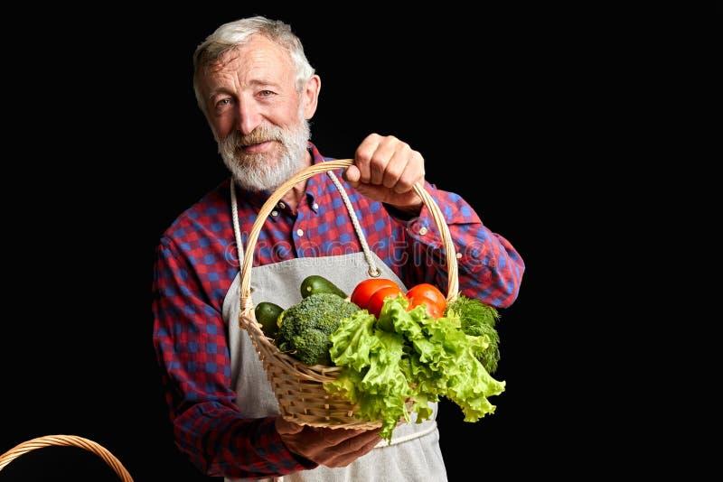 Добросердечный зрелый человек деревни скомплектовал вверх от парника некоторые свежие овощи стоковые изображения