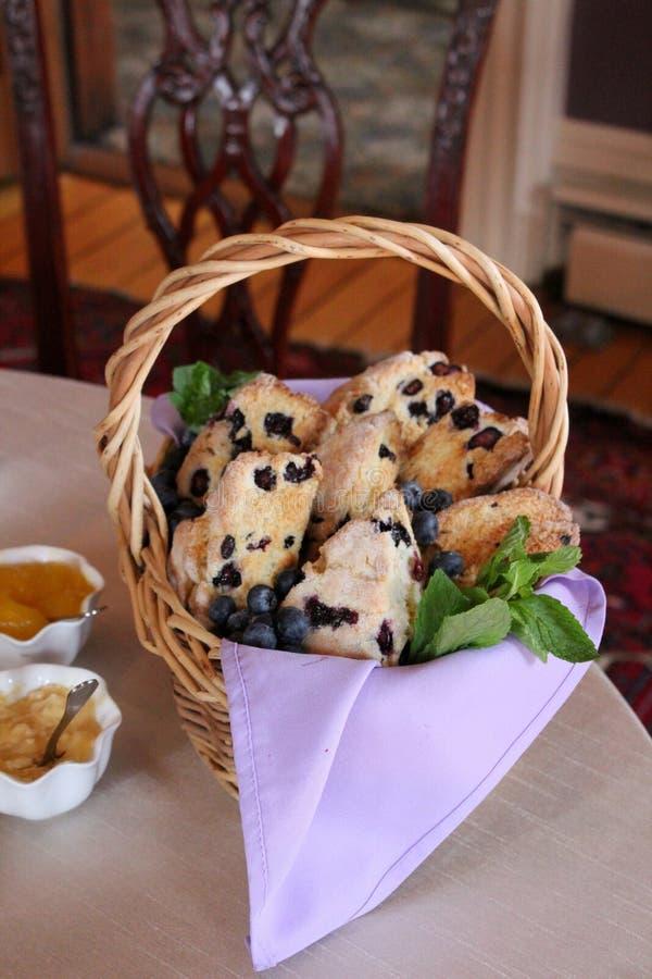 Добро пожаловать видимость корзины хлеба со свежими испеченными scones голубики, варенья и студни установили рядом с камином на о стоковые изображения