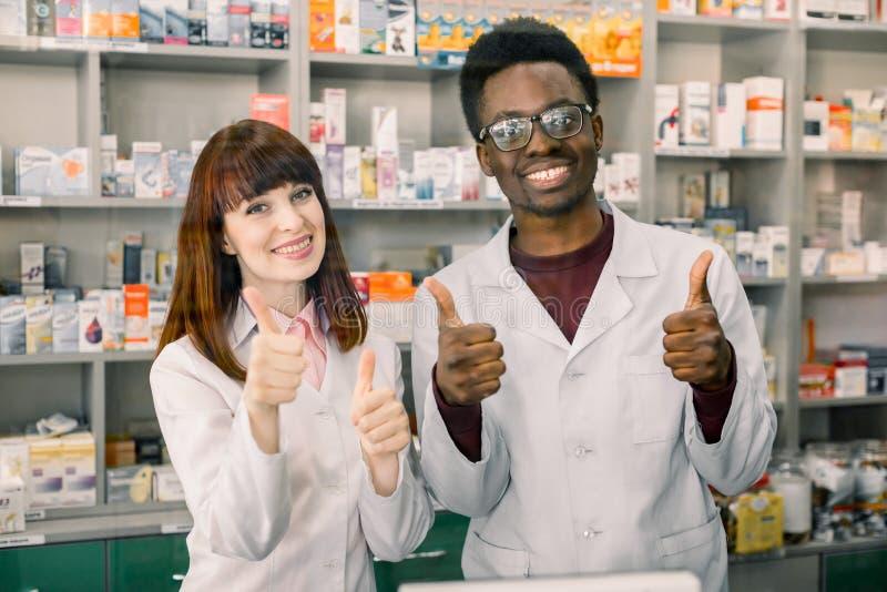 Добро пожаловать в аптеке Счастливый усмехаться 2 аптекаря, африканский человек и кавказская женщина, показывая жестами большие п стоковые изображения