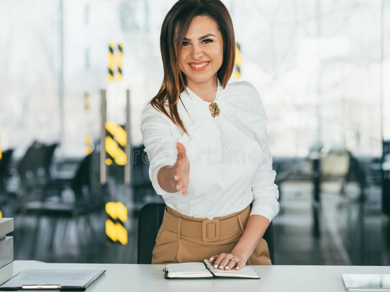 Добро пожаловать дружелюбной занятость дамы протягиванная рукой стоковое фото rf