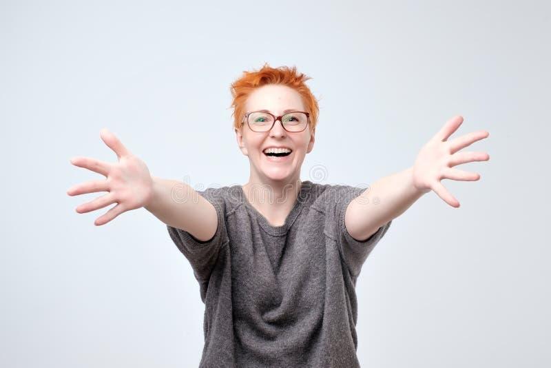 Добро пожаловать или приятно познакомиться концепция Европейская женщина в серых свитере и стеклах с протягиванным рукопожатием р стоковые фотографии rf