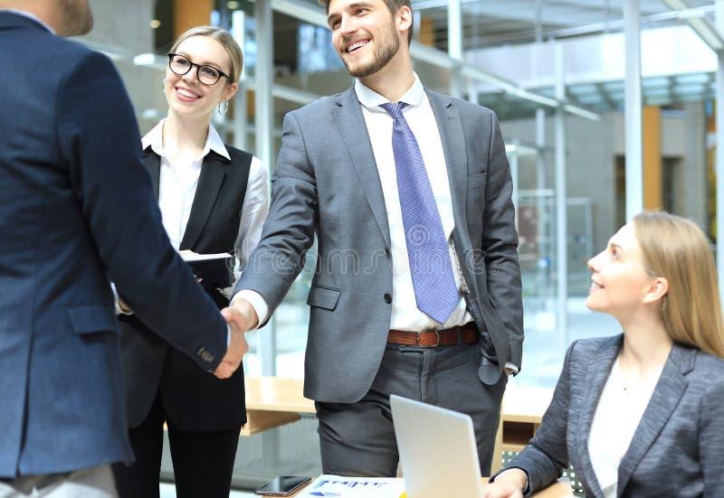 Добро пожаловать к нашей команде Молодые современные бизнесмены тряся руки пока работающ в творческом офисе стоковое изображение
