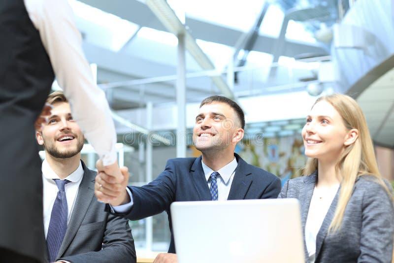 Добро пожаловать к нашей команде Молодые современные бизнесмены тряся руки пока работающ в творческом офисе стоковые изображения rf