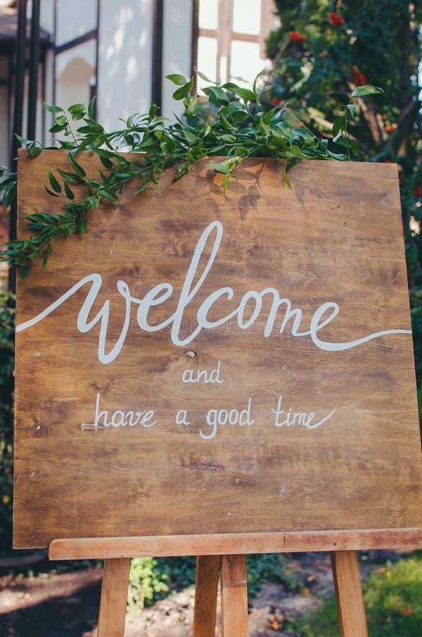 Добро пожаловать к нашему торжеству Рукописная доска знака текста каллиграфии на деревянной панели в саде с хворостиной дерева стоковые изображения