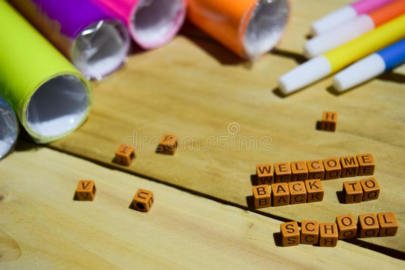 Добро пожаловать назад к школе на деревянных кубах с красочной бумагой и ручке, воодушевленности концепции на деревянной предпосы стоковая фотография