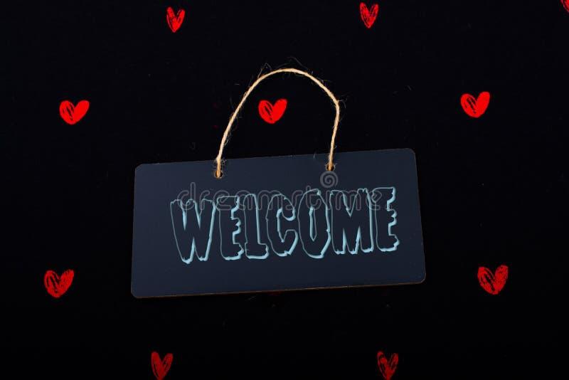 Добро пожаловать на черной доске объявлений с красными сердцами вокруг стоковые фото