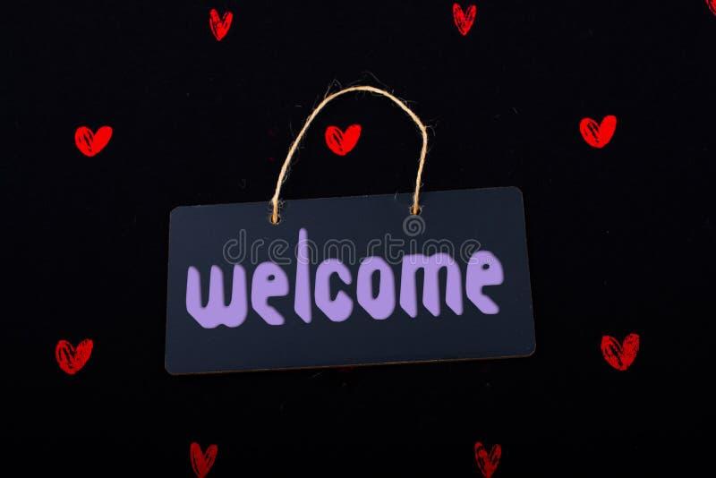 Добро пожаловать на черной доске объявлений с красными сердцами вокруг стоковая фотография