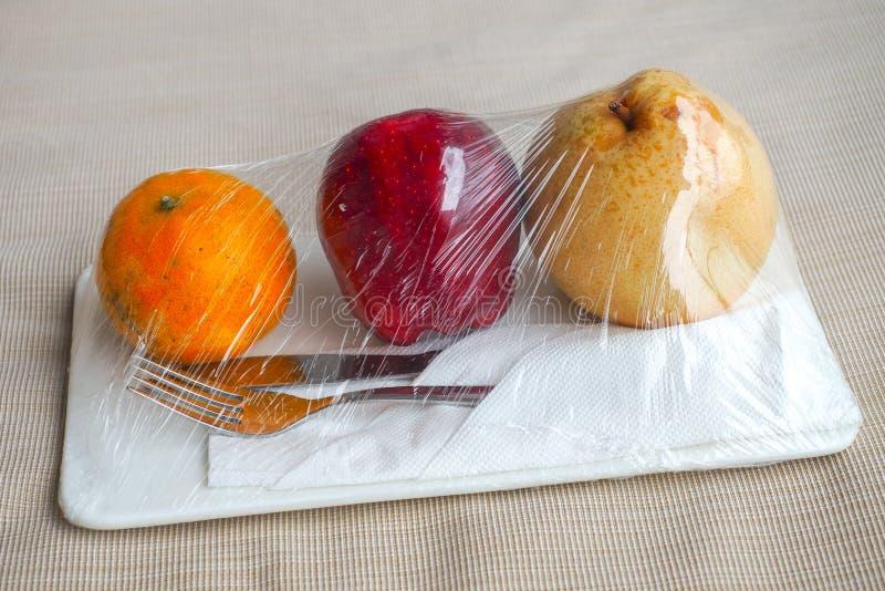 Добро пожаловать плод в гостиничном номере с яблоком и апельсином груши положил на белую кровать готовую для еды с серебряными но стоковые изображения rf