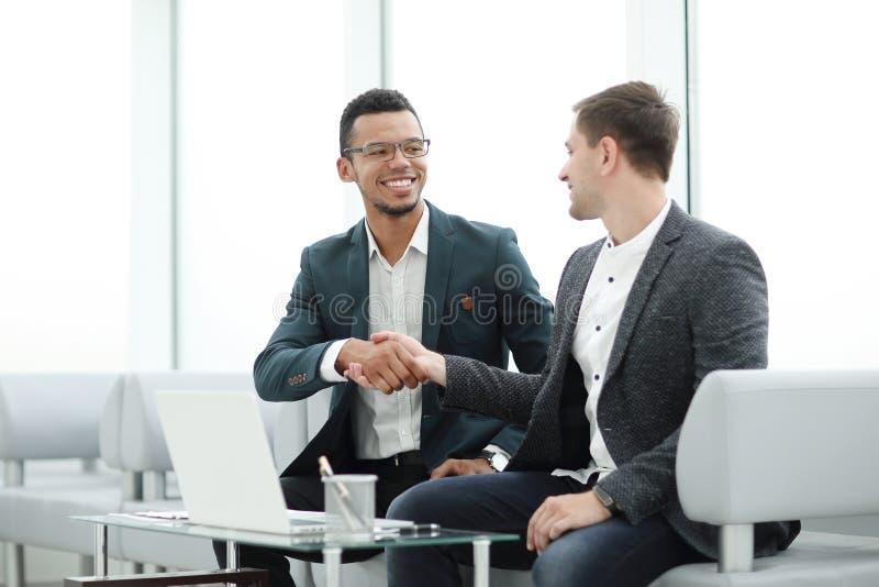 Добро пожаловать рукопожатие бизнесменов в лобби банка стоковое изображение rf