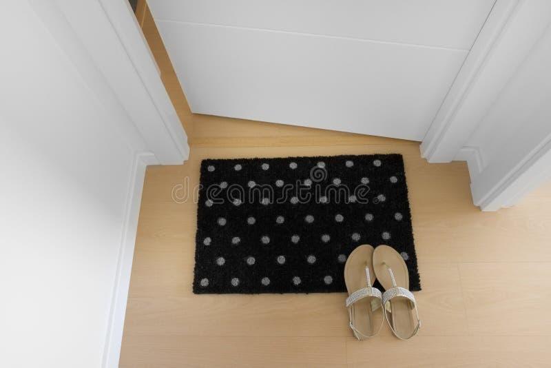 Добро пожаловать дом на черной циновке стоковые фотографии rf