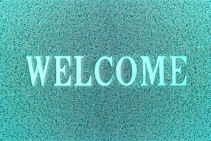 Добро пожаловать Cyan коврик у входной двери Добро пожаловать предпосылка ковра стоковые изображения rf