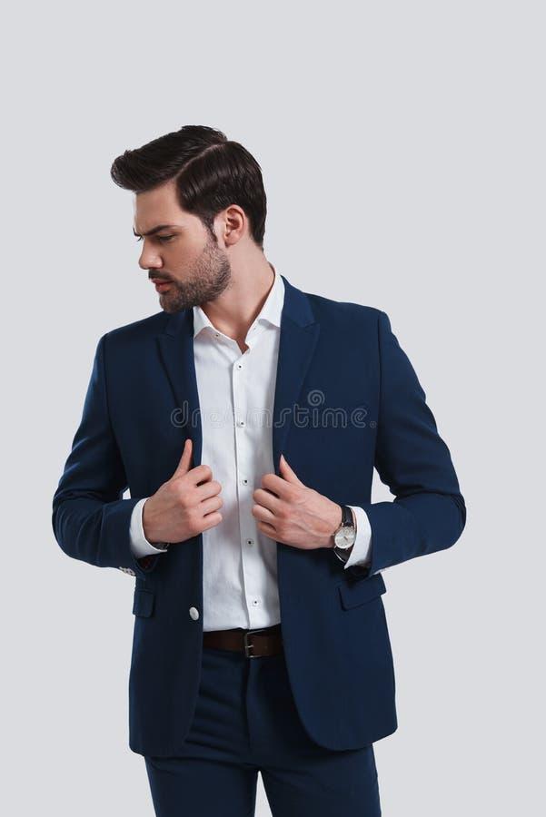 Доверие и харизма Красивое adjusti костюма молодого человека полностью стоковая фотография rf
