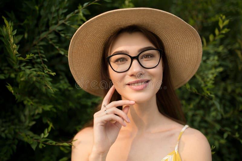 Довольнаяся женщина в желтых комбинезоне и шляпе стоит в городе на улице стоковые фотографии rf