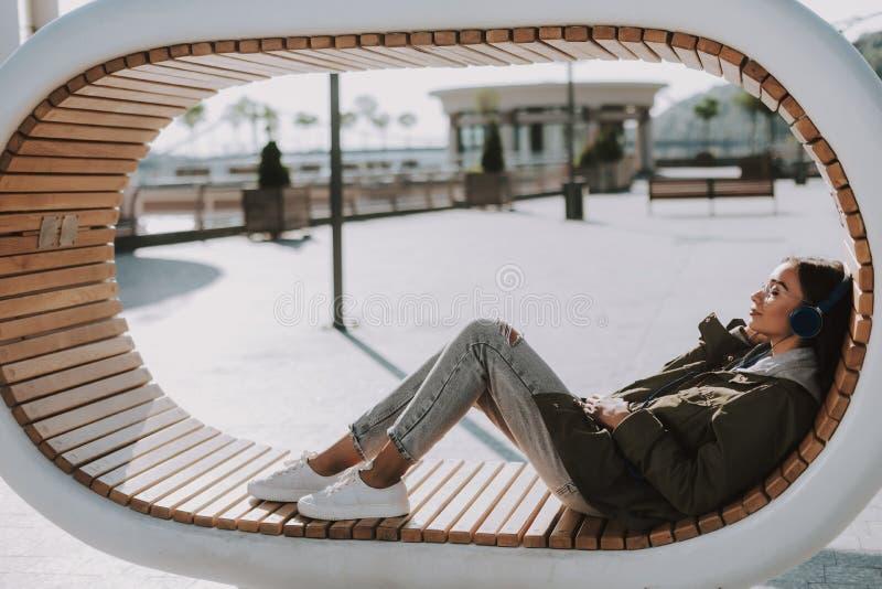 Довольная молодая женщина слушая музыку outdoors стоковое фото