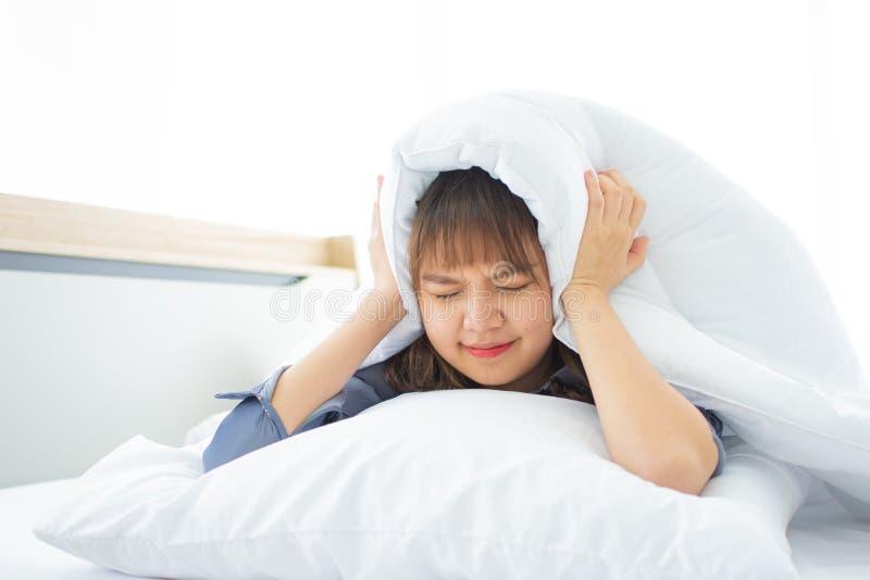 Довольно азиатская женщина не может спать хорошо на ее кровати стоковое изображение rf