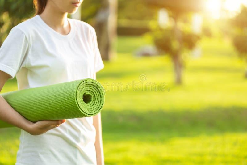 Довольно азиатская циновка йоги зеленого цвета удерживания и подготавливает для делать йогу e стоковое фото rf