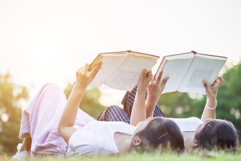 Довольно азиатские близнецы девушка или студенты читая книгу в публике стоковое изображение rf