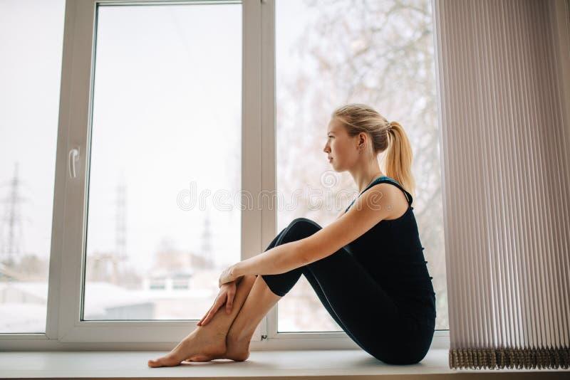 Довольно атлетическая белокурая девушка в черном sportswear сидя около окна смотря вне релаксация pilates пригодности принципиаль стоковое фото rf