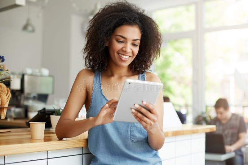 Довольно африканская студентка отдыхая в кафе усмехаясь смотрящ экран таблетки стоковые фотографии rf