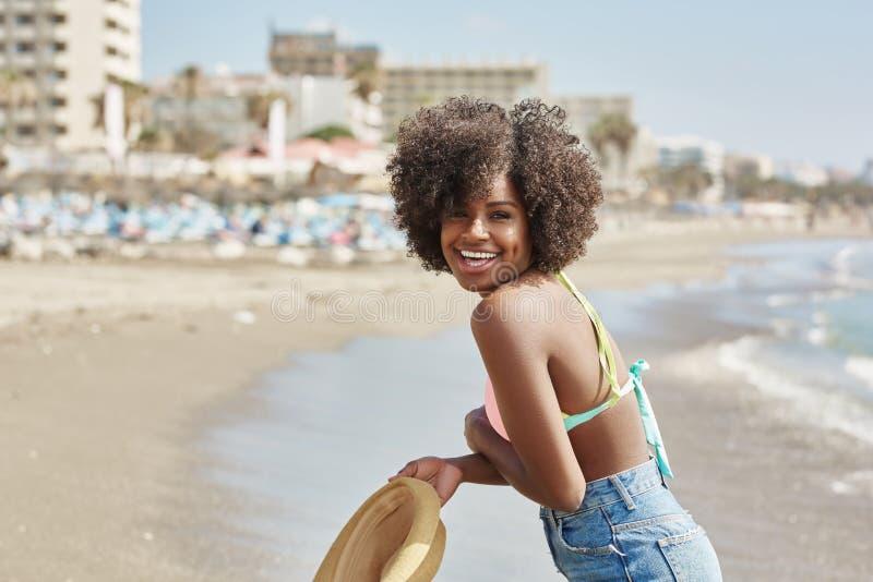 Довольно афро американская девушка держа шляпу на смеяться над пляжа стоковое изображение rf