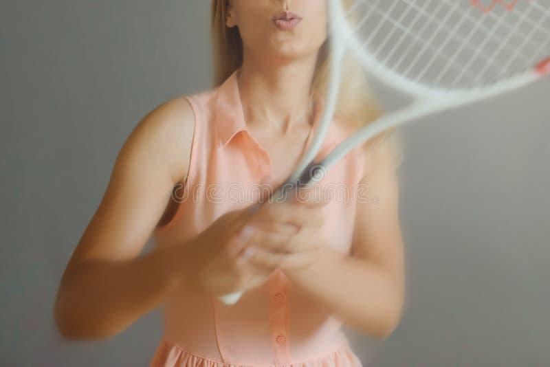 Довольно белокурая девушка с палитрой тенниса стоковая фотография rf