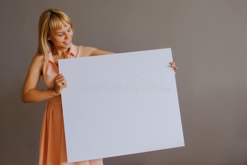 Довольно белокурая девушка с whiteboard стоковое изображение rf