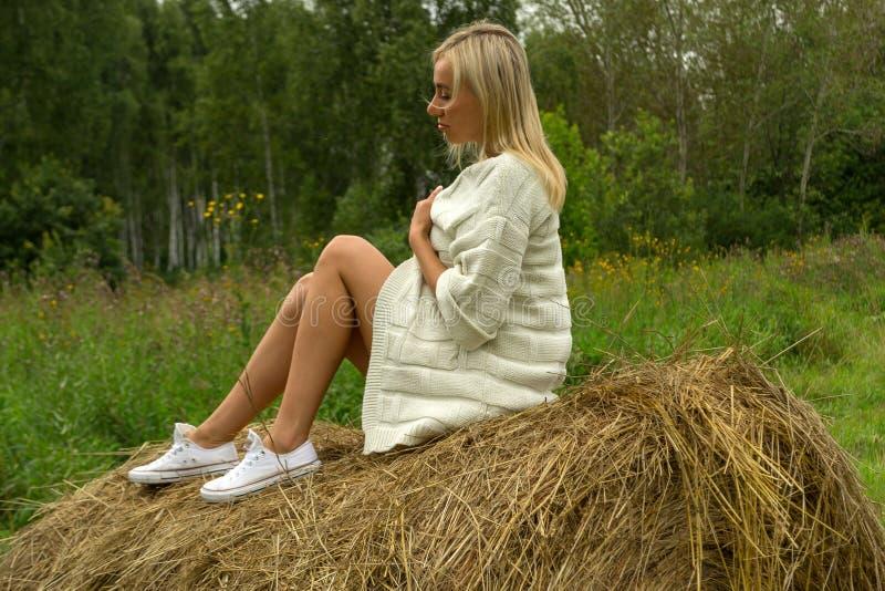 Довольно белокурая женщина в a в куртке связанной белизной шерстяной сидит стоковые изображения