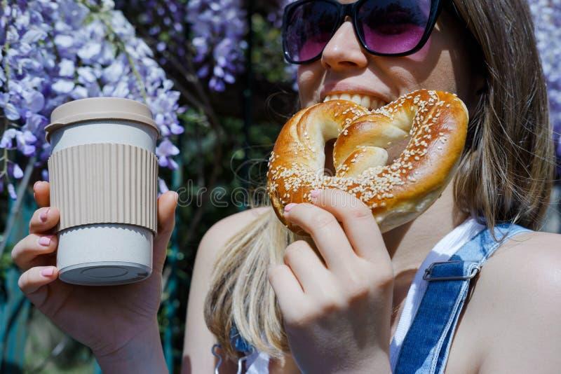 Довольно белокурая женщина держа чашку кофе и сладостный крендель в a стоковые фото