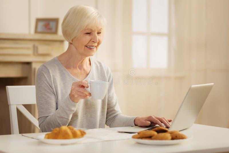 Довольно белокурый смотря экран ее компьютера стоковое фото