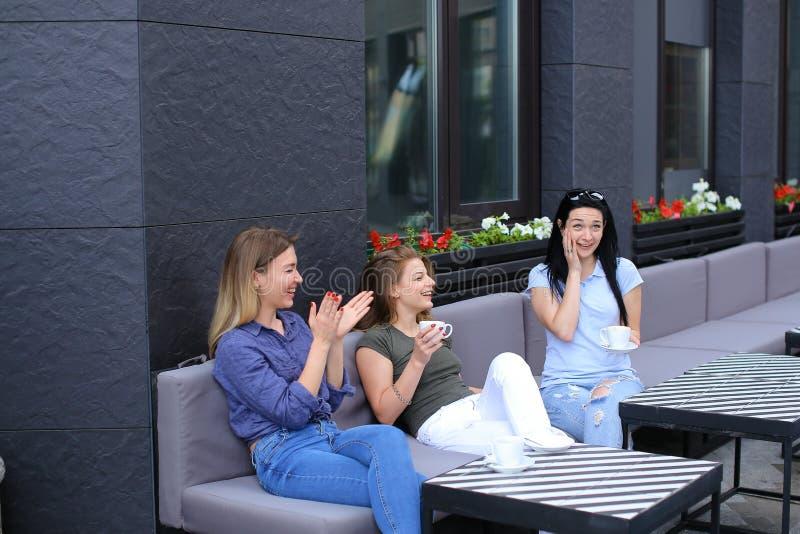 Довольно женские друзья смеясь над на кафе и gossiping, выпивая кофе стоковое изображение