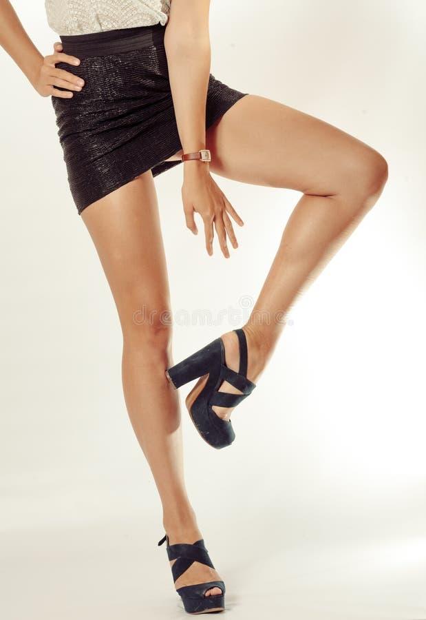 Довольно женские ноги в черных высоких пятках, при одна поднятая нога стоковые фотографии rf