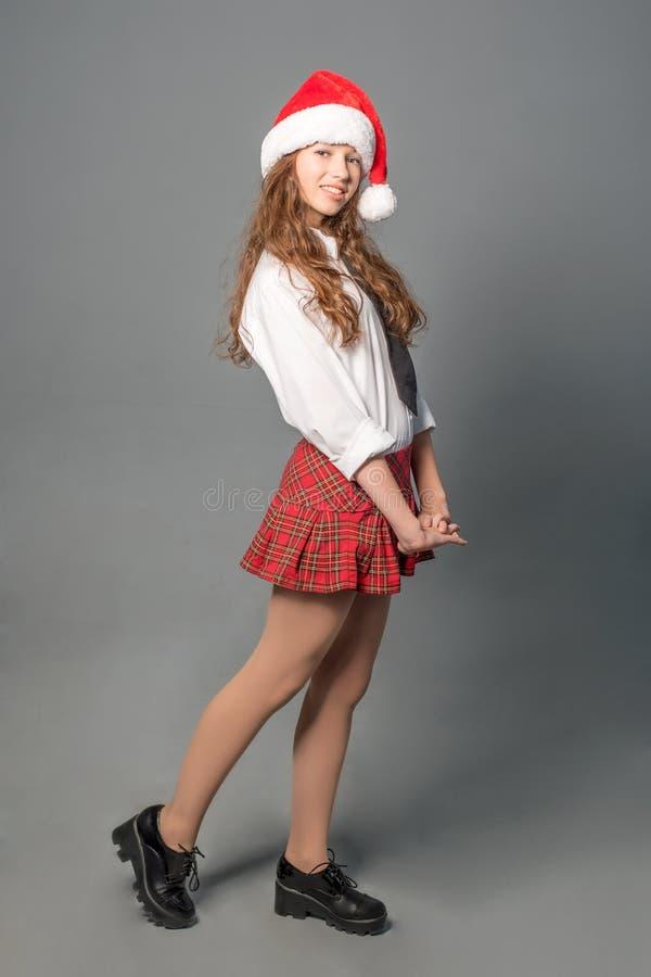 Довольно застенчивая студентка в коротких школьной форме и шляпе Санты стоковые фото
