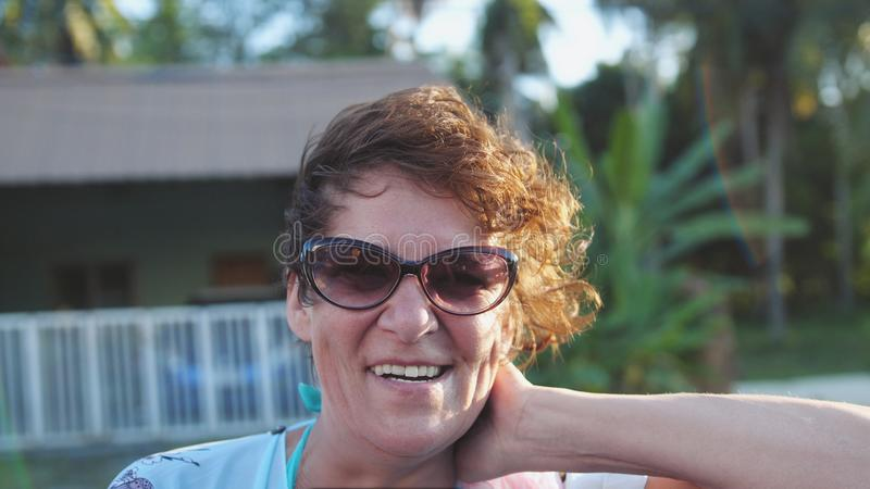 Довольно зрелая женщина в постаретых нося солнечных очках наслаждаясь солнцем лета Счастливая усмехаясь женщина имея потеху на ве стоковое изображение rf