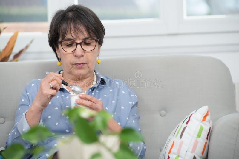 Довольно зрелая женщина есть югурт дома стоковое изображение rf