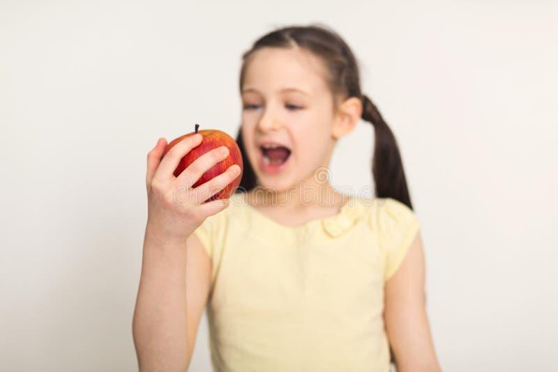 Довольно милая маленькая девочка сдерживая красное яблоко над белой предпосылкой стоковые фотографии rf