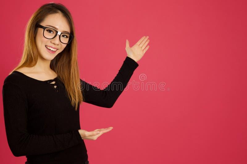 Довольно молодая азиатская женщина в студии указывая с обеими руками стоковое изображение