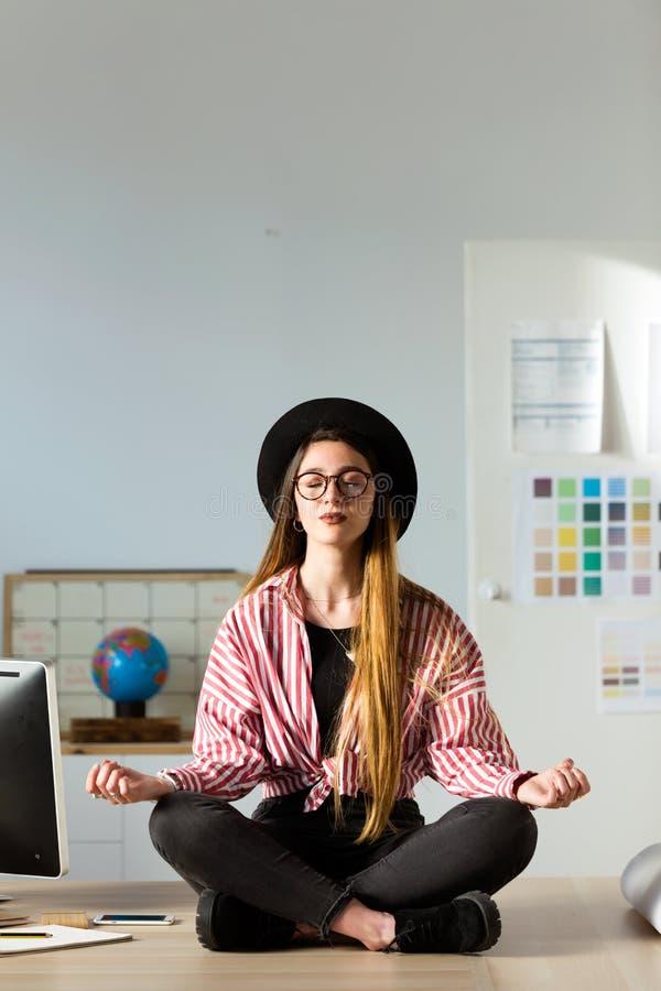 Довольно молодая бизнес-леди делая йогу на таблице в офисе стоковые фото