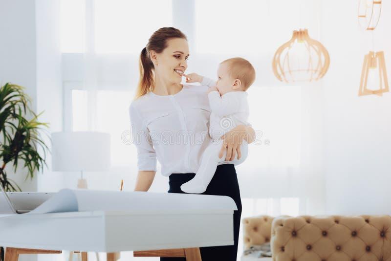 Довольно молодая женщина держа ее ребенка стоковое фото