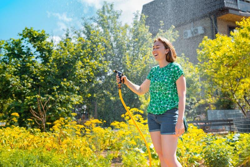 Довольно молодая женщина имея потеху в саде лета со шлангом сада брызгая дождь Концепция утехи и хобби лета r стоковое фото