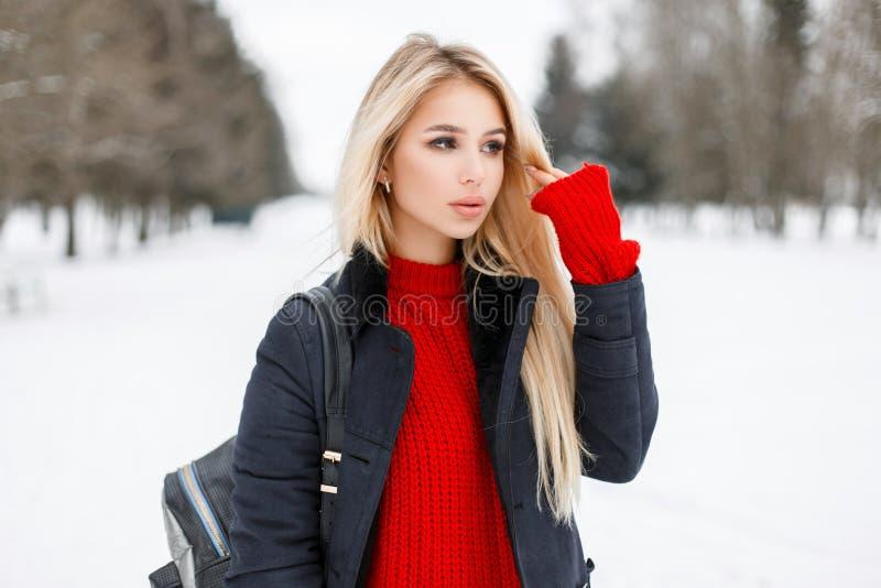 Довольно молодая модельная девушка в пальто моды с красным свитером стоковые изображения