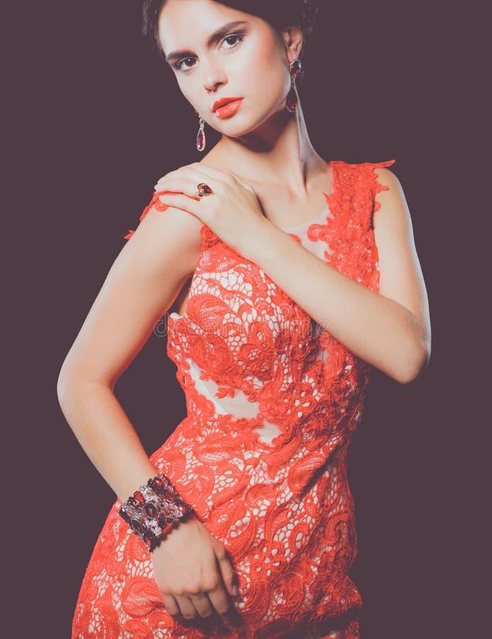 Довольно молодая модельная женщина с темными волосами в изумительном длинном красном платье стоковое фото