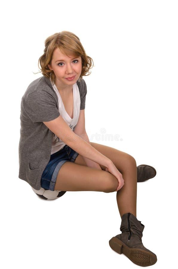 Довольно молодое белокурое усаживание женщины стоковые фото