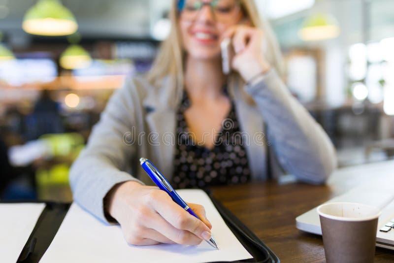 Довольно молодые писчие бумаги бизнес-леди пока использующ ее мобильный телефон в кафе стоковая фотография