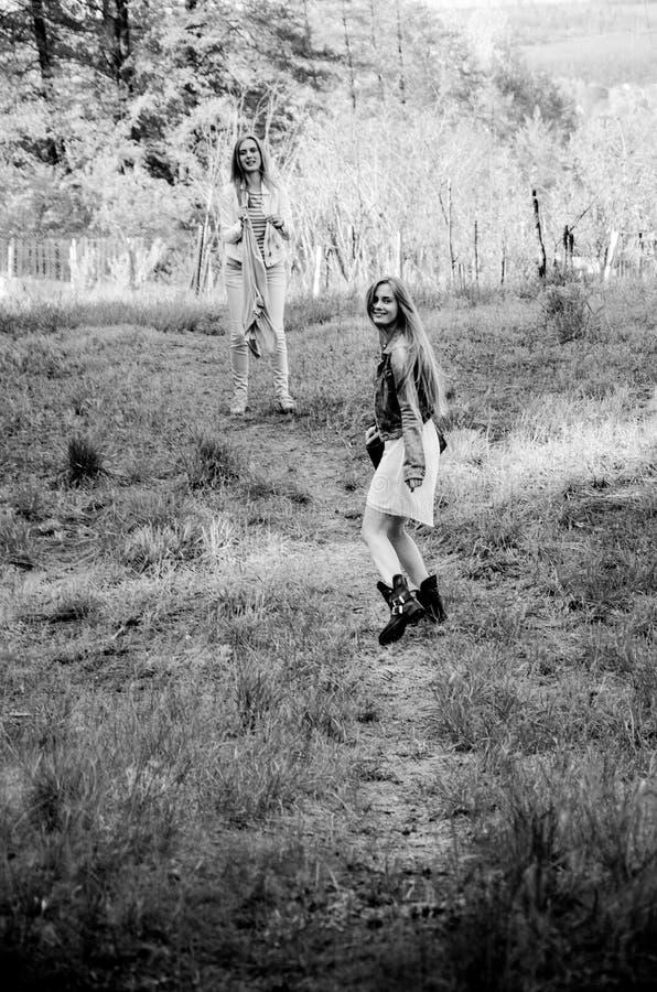 2 довольно молодых девушки близнецов идя на дорогу сельской местности стоковое изображение rf