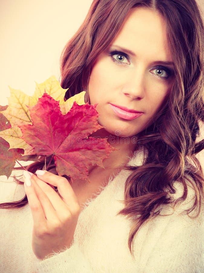 Довольно осенняя девушка с кленовыми листами в руке стоковое изображение