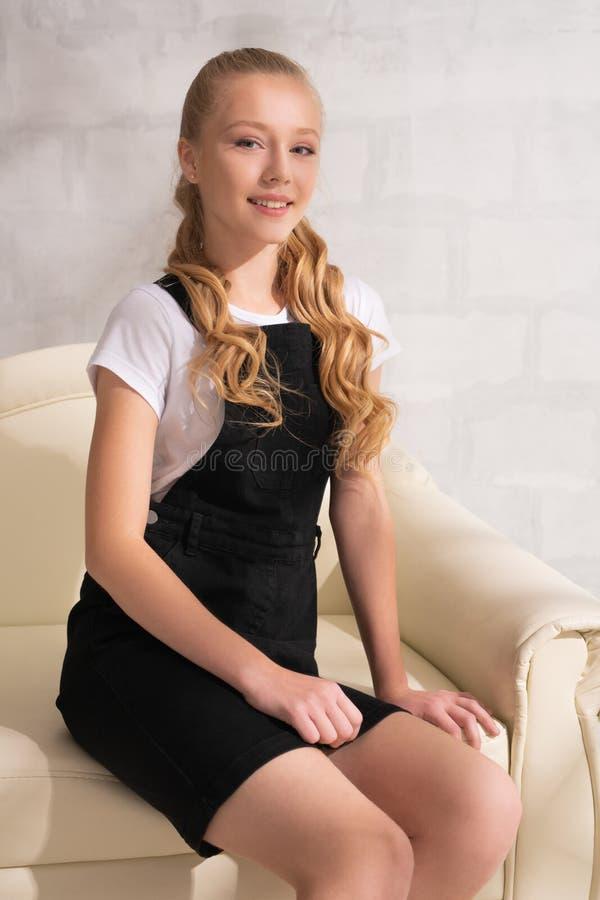 Довольно подросткового возраста девушка в белом взгляде футболки стоковое фото rf