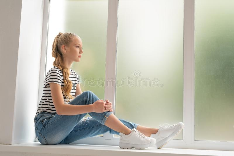 Довольно подросткового возраста девушка на съемке профиля силла окна стоковые фото