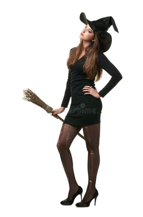 Довольно сексуальная молодая ведьма брюнет с веником стоковое фото
