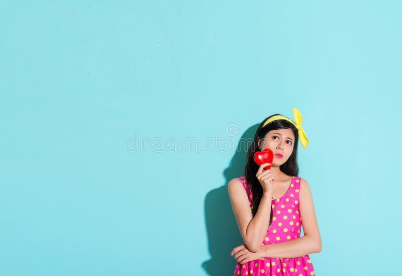 Довольно сладостная студентка стоя в голубой стене стоковое фото
