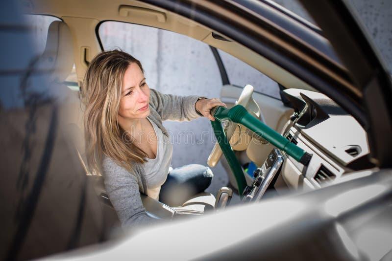 Довольно, средний достигший возраста вакуум женщины очищая интерьер автомобиля стоковая фотография rf